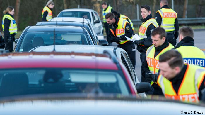 A line of police check cars on the German border