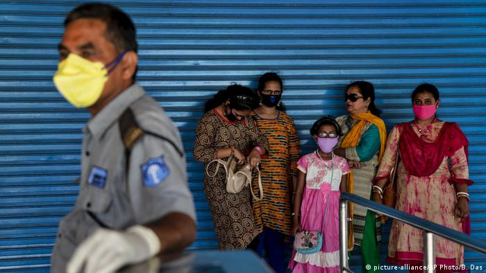 A security guard and visitors wear masks as a precaution against COVID-19 at the entrance to the zoo in Kolkata, India, Sunday, March 15, 2020