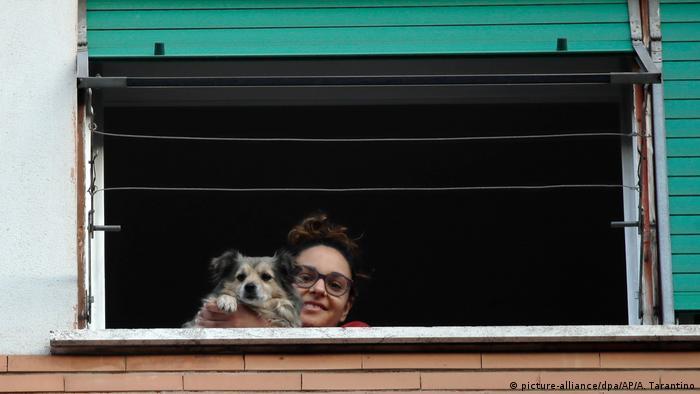 Eine Frau und ihr Hund schauen in Rom während eines Flashmobs gegen die Einsamkeit aus dem Fenster