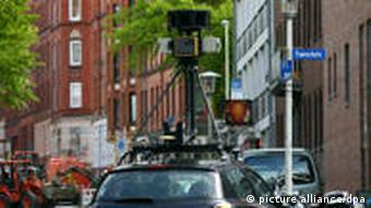 A car with a camera on top in city traffic