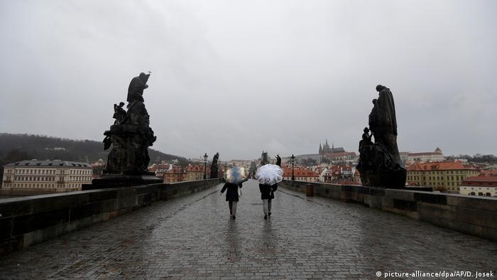 Duas pessoas circulam por ponte com guarda-chuva