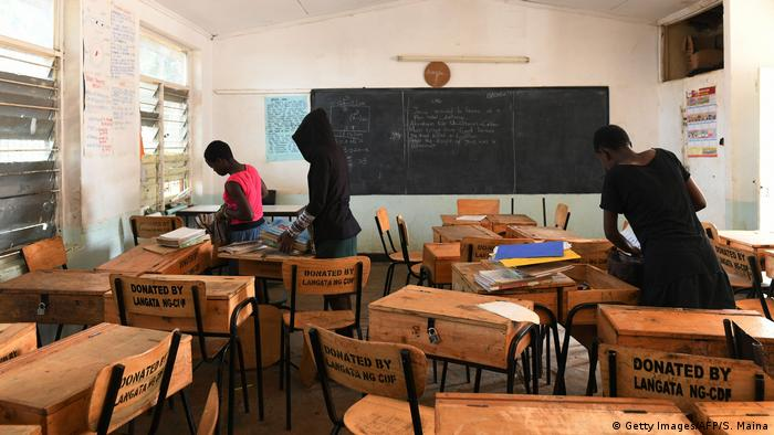 Children pack their books in an nearly empty classroom on Kenya