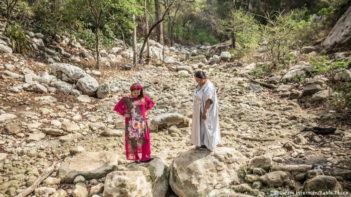 En este lugar solía correr el agua. Hoy, Janeth Pareja y Norka Ortiz se detienen sobre las piedras en el lecho de arroyo Aguas Blancas.