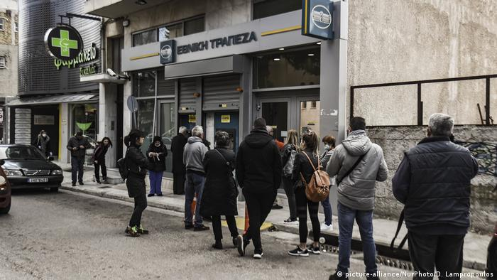 Customers wait in a queue to receive a card to allow them to ender in a bank in Athens