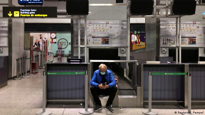 Man waits for his flight as he wears protective mask against coronavirus