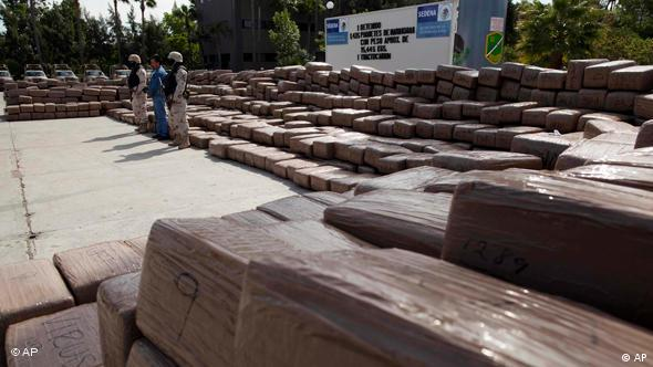 Soldiers guard a suspect next to packages containing 15, 445 kilograms of marijuana seized in a truck
