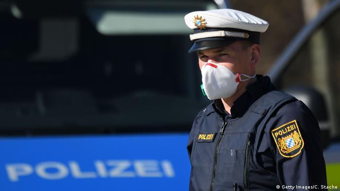 Policial de máscara num posto de fronteira entre a Áustria e a Alemanha