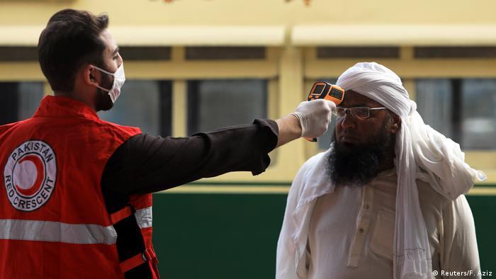 A worker checks a man's temperature following an outbreak of the coronavirus disease
