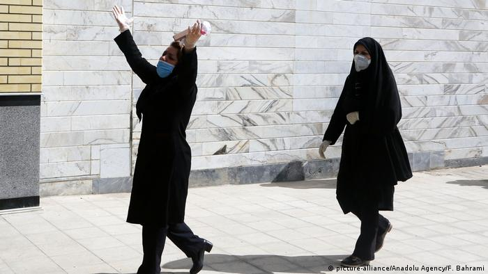 Two Iranian women in black during a funeral from the coronavirus outbreak