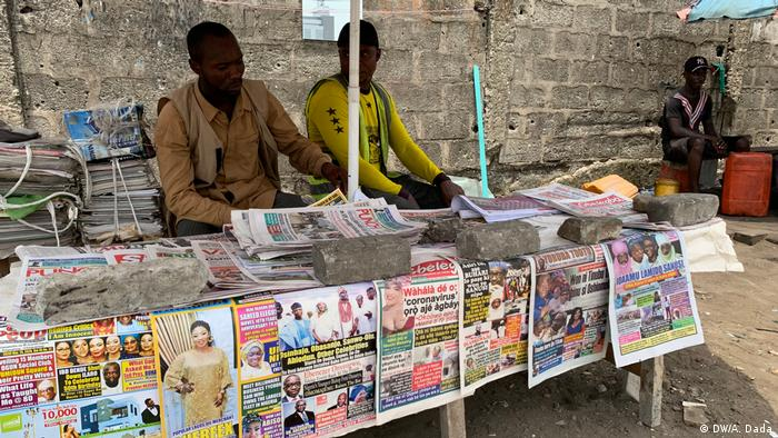Two men sit at a newspaper stand in Lagos (DW/A. Dada)
