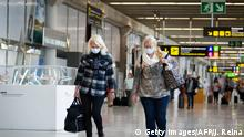 Two tourists wearing face masks walk at the airport in Palma de Mallorca on March 16, 2020. - Spain has registered nearly 1,000 new COVID-19 infections over the past 24 hours, raising the total number of cases to 8,744. In order to rein in the virus, Spain has declared a state of alert, shutting all but essential services and ordering its population of 46 million people to stay at home. People are only authorised to go out to buy food or medicine, to go to work or to get medical treatment. (Photo by JAIME REINA / AFP) (Photo by JAIME REINA/AFP via Getty Images)