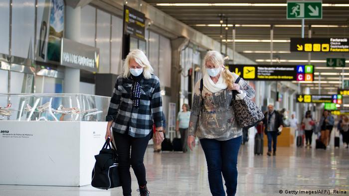 Spanien Zwei Touristen mit Gesichtsmasken am Flughafen in Palma de Mallorca (Getty Images/AFP/J. Reina)