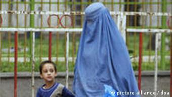 Eine afghanische Frau mit Burka, geht mit ihrem Sohn in der Hauptstadt Kabul eine Strasse entlang (Foto: dpa)