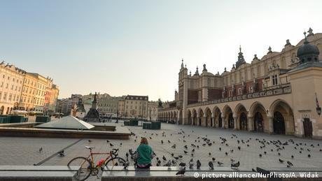 A woman cyclist sits on a wall at the edge of an empty market place in Krakow, Poland