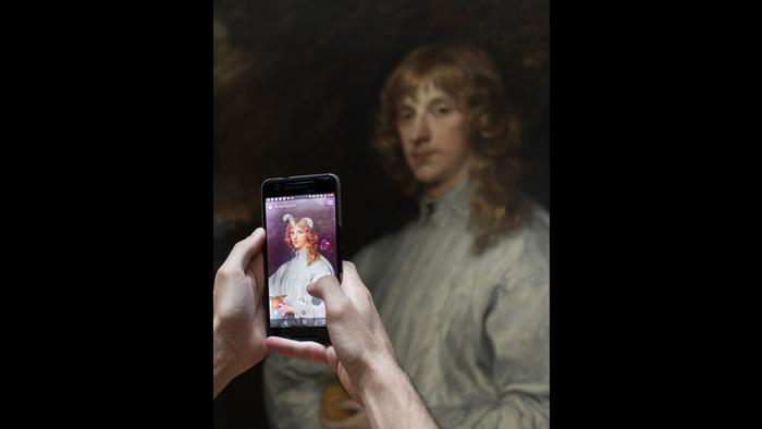 Two hands hold up a cell phone to take a photograph of a painting (Foto: Antonio Perez Rio)