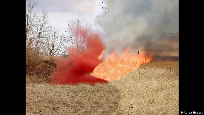 Red-orang fire blazes on the edge of a field of brown, dried-out grass (Foto: Aaron Hegert)