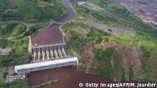 Aerial view taken on December 16, 2013 in Inga shows Inga 1 (rear) and Inga 2 (front) power plants on the Congo river. The Democratic Republic of Congo and South Africa vowed on October 16, 2015 to step up work on a massive new hydroelectric dam on the Congo River that could provide power to the entire continent. The Inga 3 Basse Chute project near Matadi would divert Congo River waters into a 12-kilometre (7.5-mile) channel and then pass them through a 100-metre-high (330-foot) hydropower dam in the Bundi Valley before releasing the water back into the river. The intake would be above the existing Inga 1 and Inga 2 dams, and the outflow downstream from both. AFP PHOTO/MARC JOURDIER (Photo credit should read MARC JOURDIER/AFP via Getty Images)