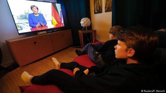 Crianças assistem a pronunciamento da chanceler federal Angela Merkel na televisão