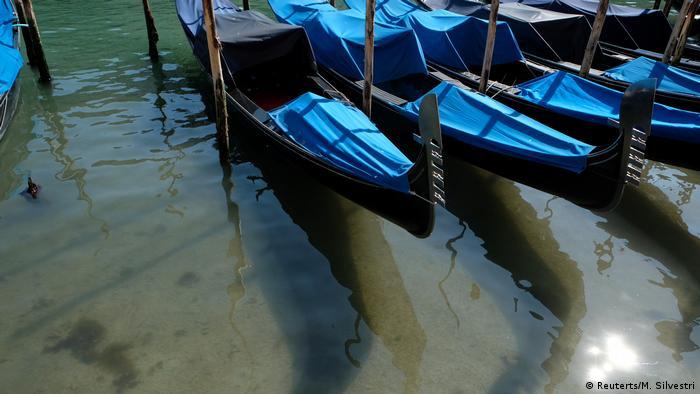 Gôndolas nas águas claras dos canais de Veneza