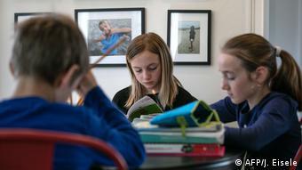 Tres niños estudiando.