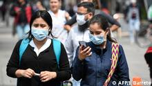Women wear face masks as a precautionary measure against the spread of the new coronavirus, COVID-19, in Bogota on March 18, 2020. - Colombian President Ivan Duque declared a state of emergency, asking citizens older than 70 to remain indoors. (Photo by Juan BARRETO / AFP)