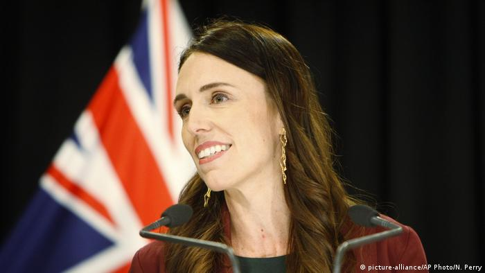 New Zealand Prime Minister Jacinda Ardern stands before her nation's flag