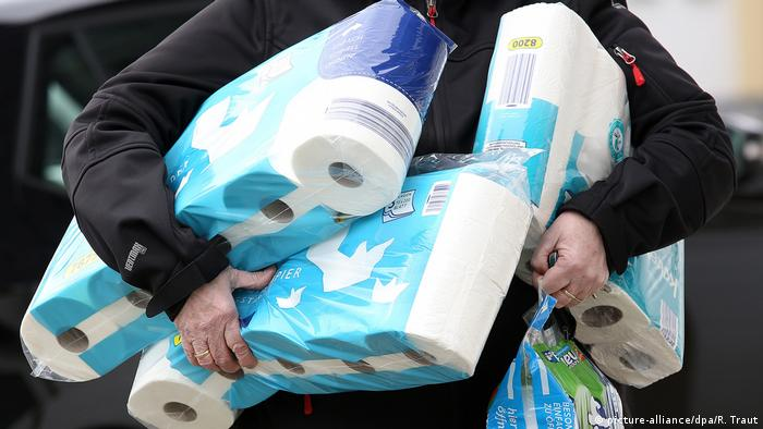 A man carries toilet paper (picture-alliance/dpa/R. Traut)