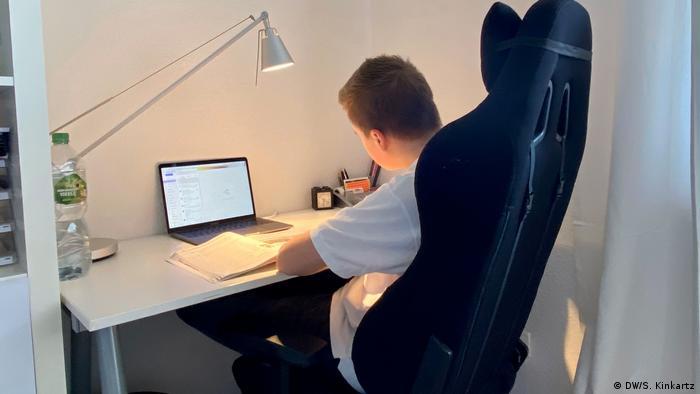 Ein Junge sitzt am Schreibtisch vorm Laptop