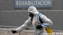 A member of the Military Emergency Unit (UME) sprays disinfectant to prevent the spread of the coronavirus disease (COVID-19) at Cabuenes Hospital in front of a sign reading Rehabilitation during a 15-day state of emergency declared to combat the outbreak of the coronavirus disease (COVID-19) in Gijon, Spain, March 18, 2020.REUTERS/Eloy Alonso