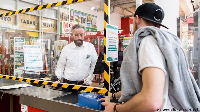 A cashier behind a protective shield at a hardware store in Germany