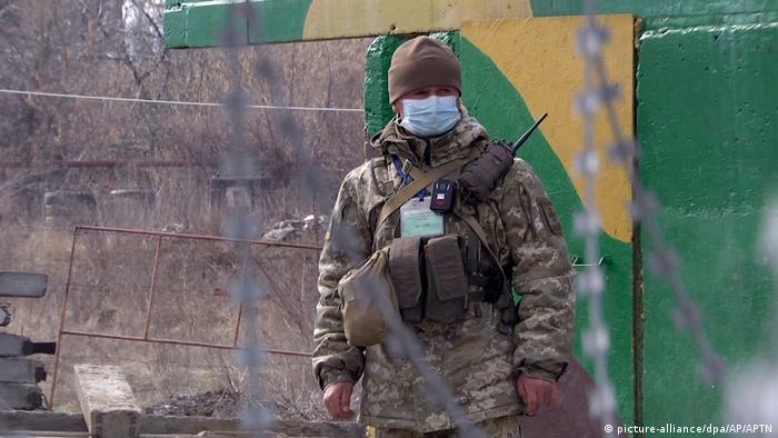 Военнослужащий в маске на линии разграничения