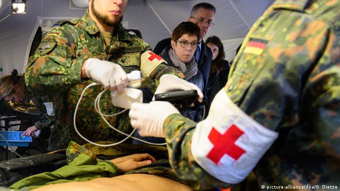 German soldiers demonstrate treating a patient as AKK looks on