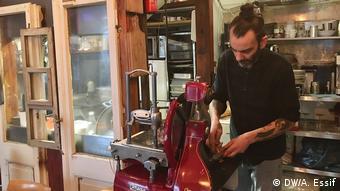 Emmano Steri, de barba e coque, corta frios em aparelho vermelho prepara comida em seu restaurante Bottega Nr. 6, em Berlim