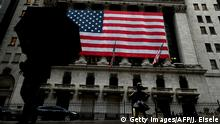 A woman walks past the New York Stock Exchange (NYSE) on March 19, 2020 at Wall Street in New York City. - Wall Street stocks fell again early Thursday as central banks unveiled new stimulus measures and US jobless claims showed an initial hit from the slowdown generated by the coronavirus outbreak. (Photo by Johannes EISELE / AFP) (Photo by JOHANNES EISELE/AFP via Getty Images)