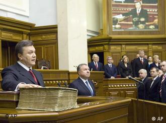 Ukraine's President Viktor Yanukovych holds his hand on the bible as he takes an oath in the parliament
