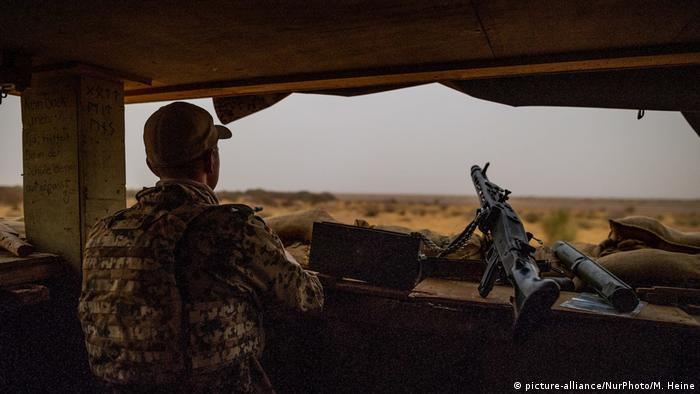 A member of the German Bundeswehr secures an area in Mali