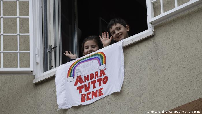 Children wave from a window