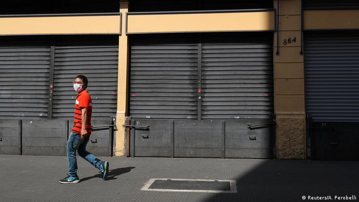 Pessoa com máscara diante de loja fechada no Rio