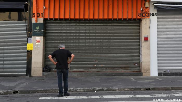 Homem parado de frente para a fachada de uma loja fechada. Eles está com as mãos na cintura e veste roupa preta.