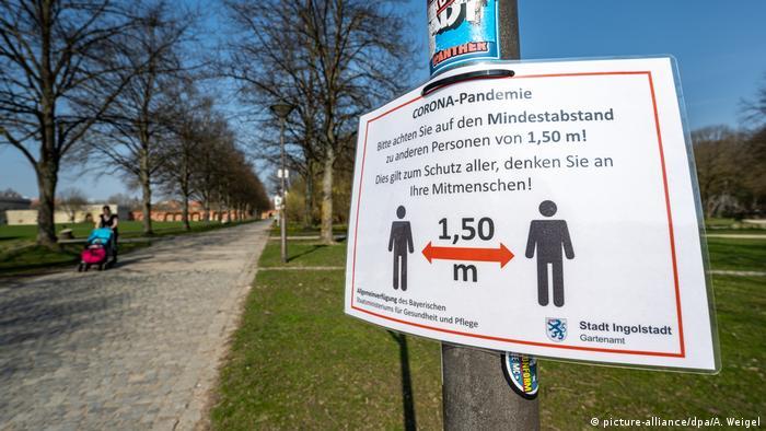 Парк в Баварии и предупреждение о соблюдении дистанции