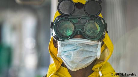A cleaner in Ethiopia wears protective goggles and mask