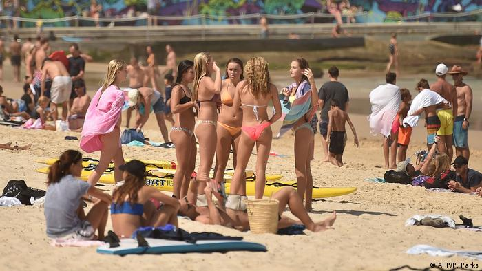 Young men and women in bathing suits close together on a beach