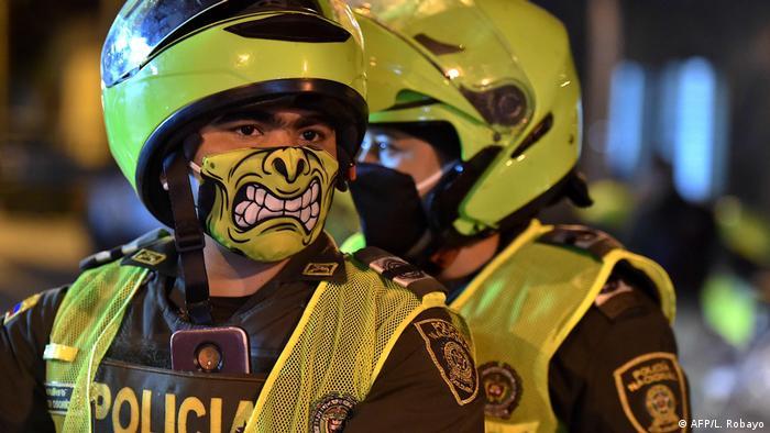 Polizist mit Mundschutz, auf dem eine Grimasse abgebildet ist (AFP/L. Robayo)