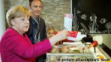 Bundeskanzlerin Angela Merkel (CDU) kauft am 19.09.2013 Matjes neben dem Geschäftführer Kron-Lastadie, Lars Gräning, in Stralsund (Mecklenburg-Vorpommern) nach einer CDU-Wahlkampfveranstaltung. Einen Tag vor der Bundestagswahl will Merkel nochmals die Wähler in ihrem Wahlkreis mobilisieren. Foto: Stefan Sauer/dpa +++(c) dpa - Bildfunk+++ | Verwendung weltweit