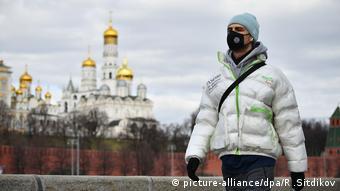 Человек в защитной маске идет по парку Зарядье на фоне золотых куполов