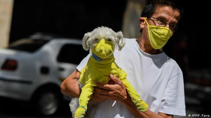 Перехожий у Каракасі намагається захистити себе та свого собаку за допомогою власноруч пошитих масок