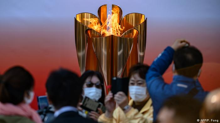 People in face masks take pictures in front of the Tokyo 2020 Olympic flame