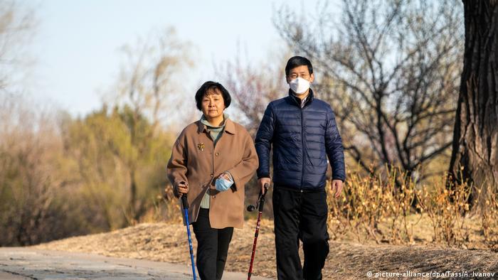 Casal faz caminhada em parque em Pequim