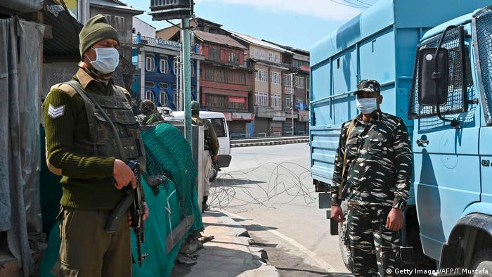 Security personnel wearing facemasks stand guard along a deserted street during a one-day nationwide Janata (civil) curfew imposed as a preventive measure against the COVID-19 coronavirus