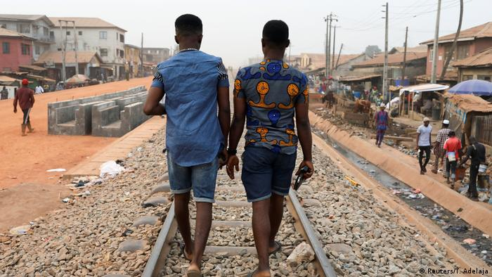 Two young men walking along the train trails, their backs to the camera